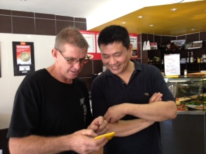 Pete showing James from Chicken Run in Dee Why photos on his phone.